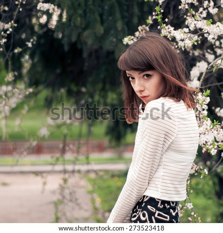 Girl posing near Cherry Blossom. Beautiful Young Woman with Sakura. Spring Flowers. - stock photo