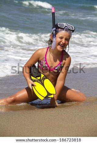 Girl posing on a beach wearing snorkeling equipment - stock photo