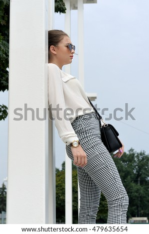 Girl posing on the background of the city. She is wearing a white shirt and plaid pants
