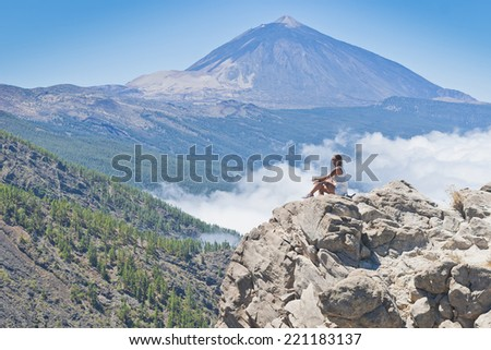 girl posing on the island of Tenerife, Spain, the Teide and the sea of �¢??�¢??clouds in the background