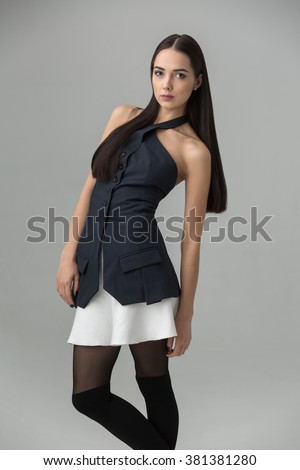 Girl posing standing in the studio on a gray background. She looks into the camera with her hands down. She wears a dark blue blouse and a white skirt. Vertical. - stock photo