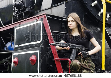 Girl posing with a gun next to the engine - stock photo