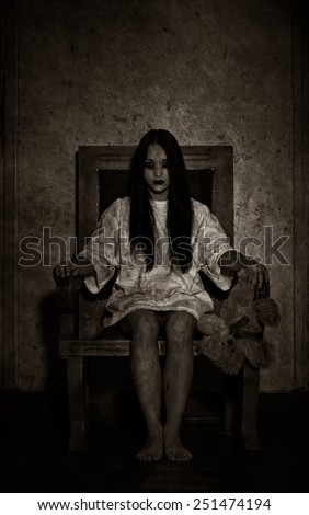 Girl possessed by the devil looks at you out of darkness. Black and white - stock photo
