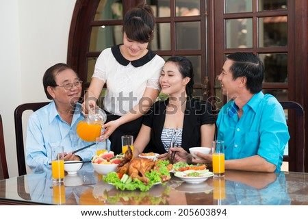 Girl pouring orange juice during the family dinner - stock photo