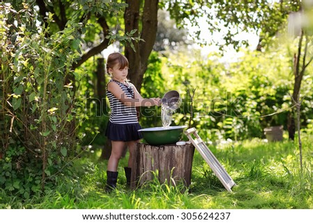 girl pours water into the bowl of the dipper, little helper, Laundry service outdoor