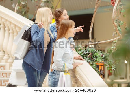 Girl power in action. Three young beautiful girls standing on the stairs of the shopping mall and looking at something interesting - stock photo