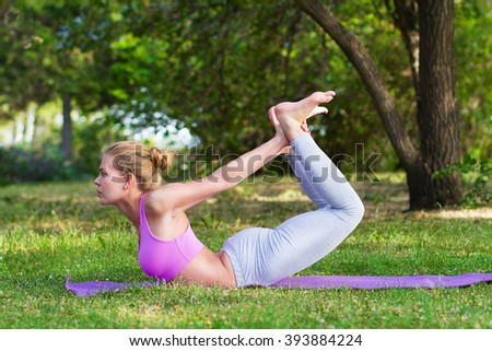 Girl practices yoga and gymnastics in the park, bow pose