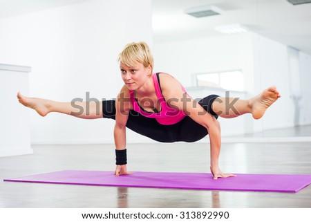 Girl practicing toga, Tittibhasana/Insect or Firefly Pose - stock photo