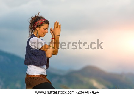 Girl practicing yoga in nature in the mountains