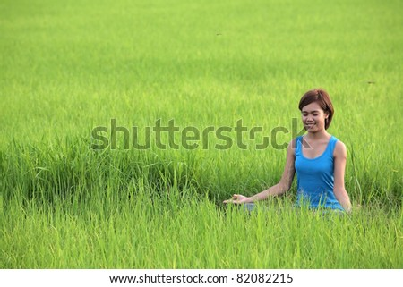 girl practicing yoga in paddy field.