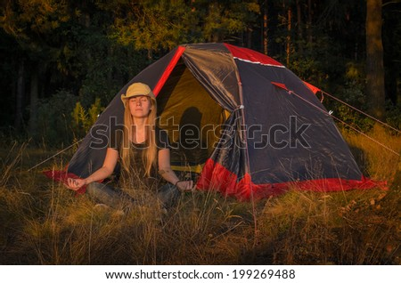 girl practicing yoga in the camp - stock photo