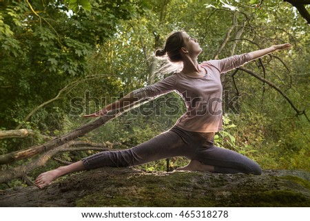 Girl practicing yoga in the morning forest.