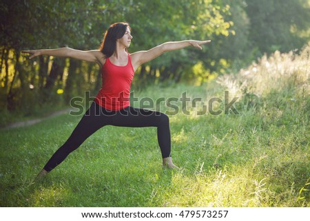 Girl practicing yoga in the park on a summer sunny day