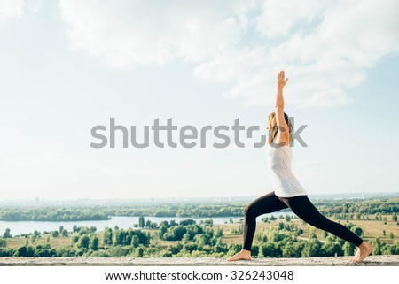 girl practicing yoga on roof. Yoga in the park - stock photo