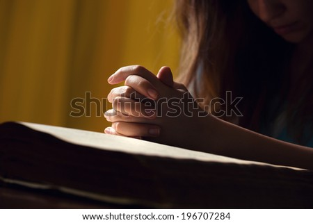 Girl praying with hands on 150 year old Bible - stock photo