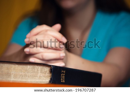 Girl praying with hands on 150 year old Bible