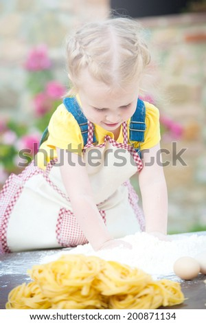 Girl preparing pasta dough on wooden table. - stock photo