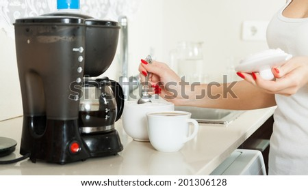 girl preparing strong coffee in the kitchen - stock photo