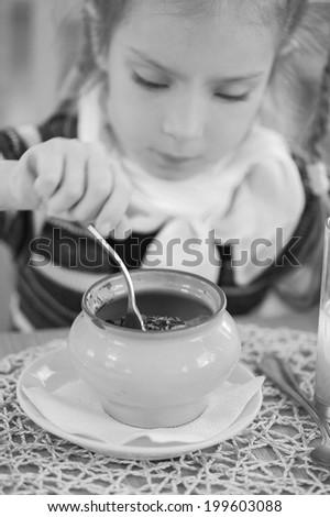 Girl-preschooler eats a tasty meal in cozy restaurant. - stock photo