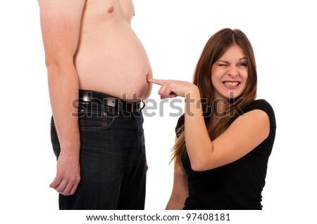 Girl pricking her boyfriends belly button - stock photo