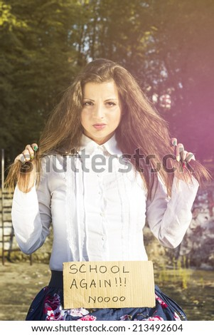 Girl pulls the hair and holding a paper with the inscription not in school - stock photo