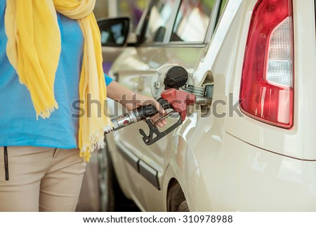 girl pumping diesel in to the tank. car fill with gasoline at a gas station. Gas station pump.  - stock photo
