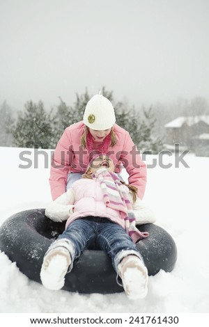 Girl pushing another girl on inner tube - stock photo
