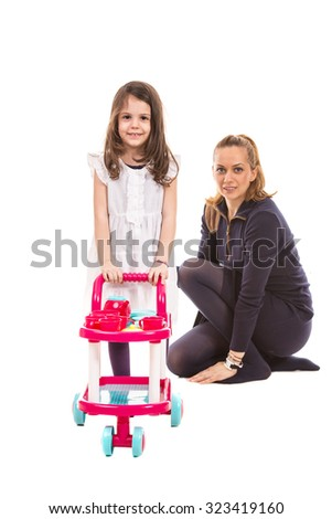 Girl pushing pram toy ad her mother sitting in background - stock photo