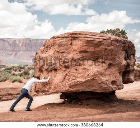 Girl pushing stone hard, impossible concept - stock photo