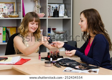 Girl puts powder on brush, under supervision of a consultant