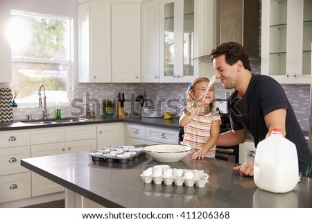 Girl putting cake mix on dadâ??s nose while they bake together - stock photo