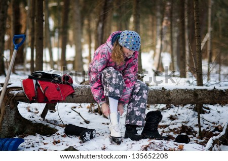 girl putting on ice skates to skate on a pond - stock photo