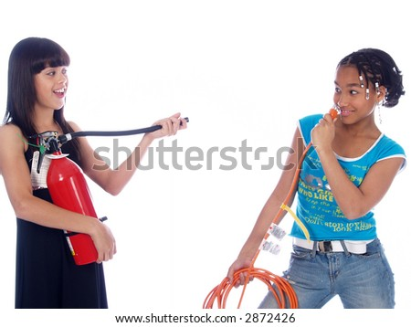 girl putting power cable in her nose, other tries to avoid disaster - stock photo