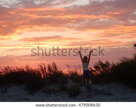 girl raised hands at sunset