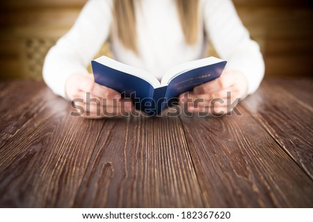 Girl reading a Bible. - stock photo