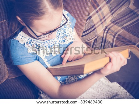 Girl reading a book at home sitting in an armchair. Photos in retro style.