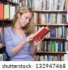 girl reading a book at the library - stock photo
