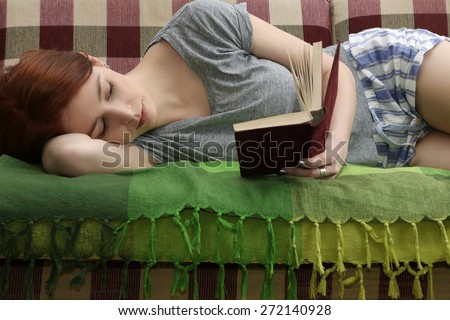 Girl reading a book Close up of lying woman reading book relaxing at home - stock photo