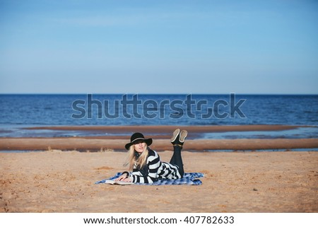 girl reading a book lying on the beach