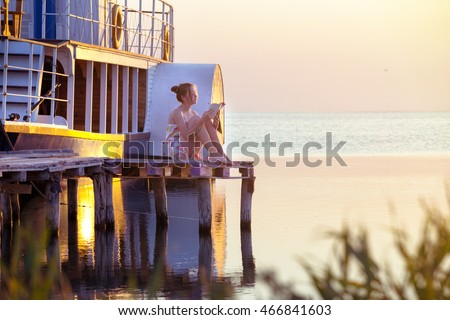 girl reading a book on a pier in the background of the sea, ship and sunset. Ukrainian landscape