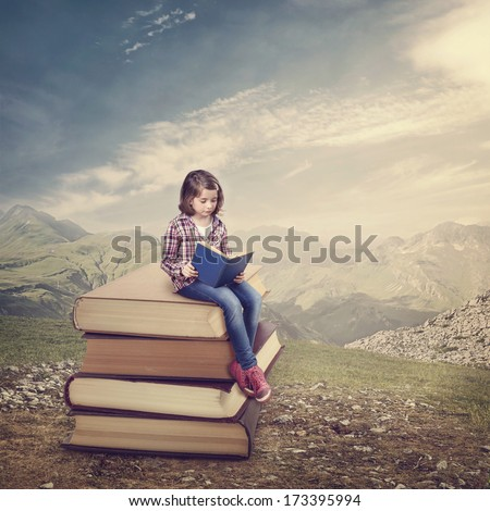 Girl reading a book on a stack of books - stock photo