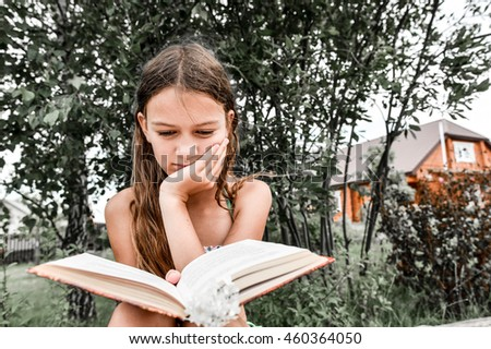 girl reading a book on nature