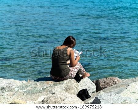 Girl reading a book on the beach. Seascape.  - stock photo