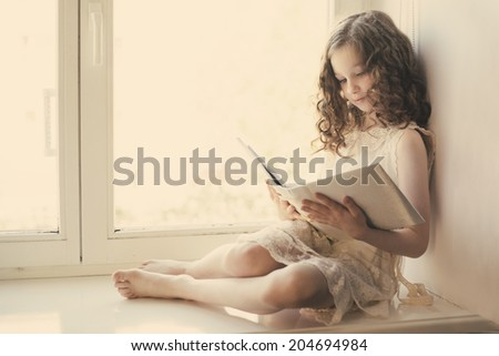 girl reading a book sitting on the window - stock photo