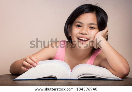 Girl reading a large book at home.