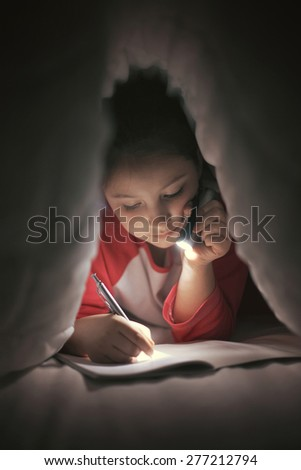 Girl reading and writing under the covers using flashlight