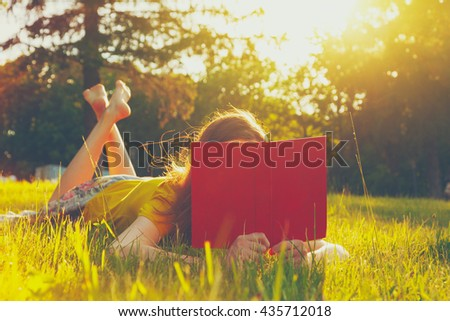 girl reading book in warm summer grass - stock photo