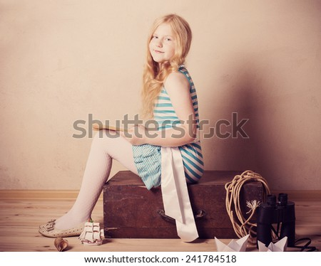 girl reading book on suitcase indoor - stock photo