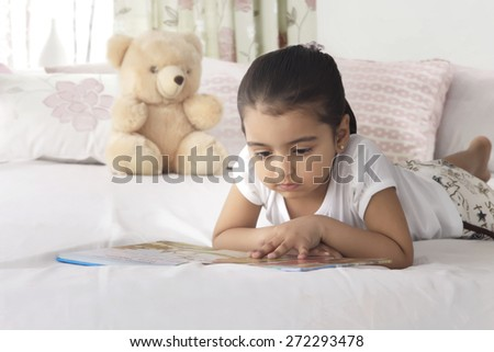 Girl reading book while lying in bed