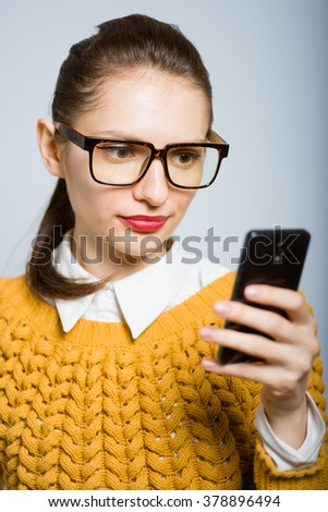 girl reading sms message on your phone, hipster glasses isolated on a gray background
